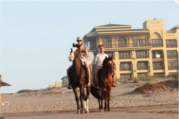 Touristen reiten auf Pferden am Strand des Mazagan Beach Resort