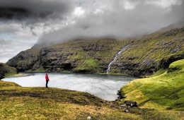 Bucht im Nebel mit Mann in roter Jacke auf den Färöer