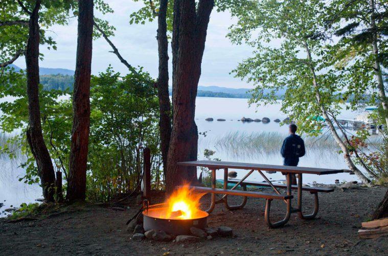 Ein Mann blickt auf den See, im Vordergrund lodert ein Feuer an einem Campingplatz