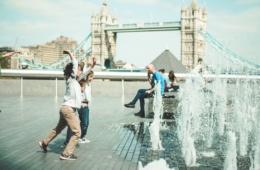 Kinder in London spielen an öffentlichem Wasserstrahl vor der Tower Bridge