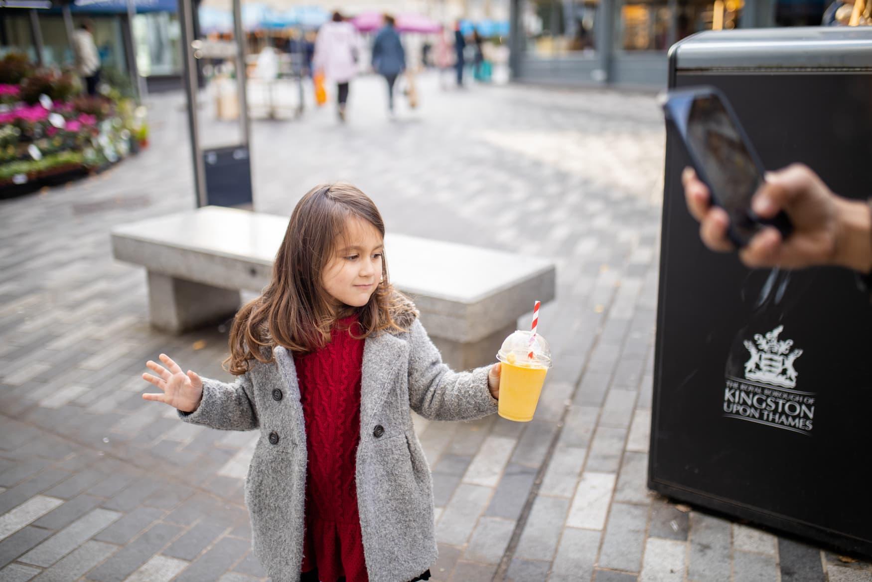 Junges Mädchen trinkt Smoothie auf den Straßen von London
