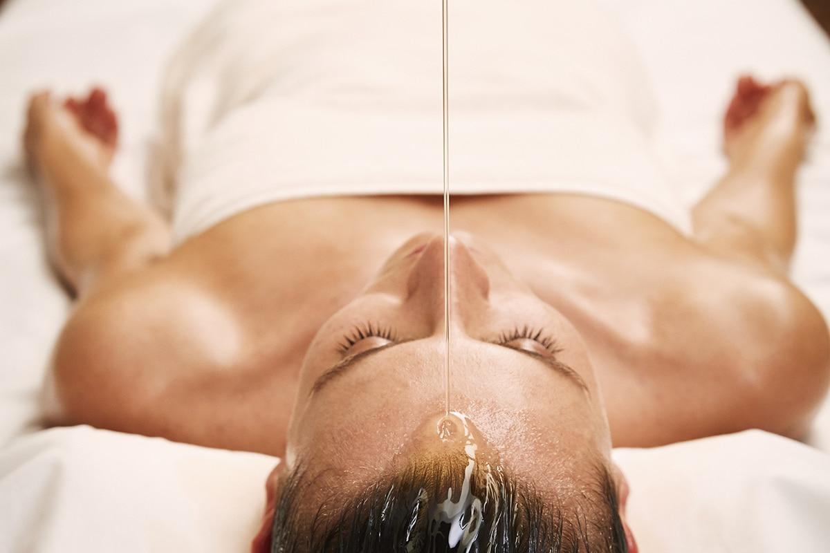 Frau wird Öl auf den Kopf gegossen bei Massage