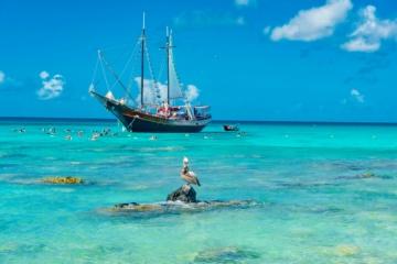 Türkisfarbenes Meer auf Aruba, Segelschiff im Hintergrund