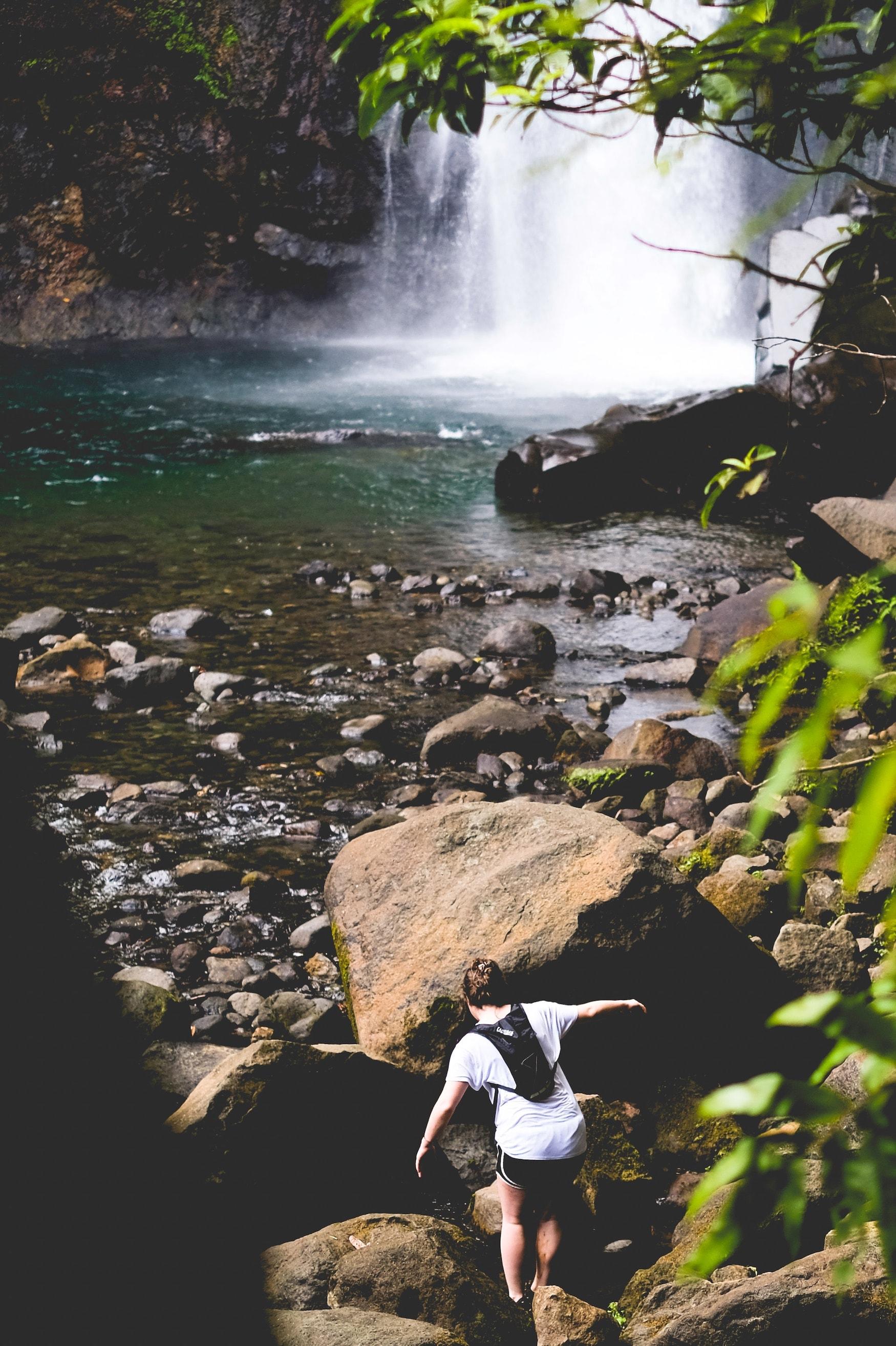 Frau klettert über Steine zu Wasserfall