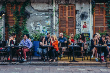 Gäste sitzen draußen vor einem Cafe auf dem Rothschild Boulevard in Tel Aviv