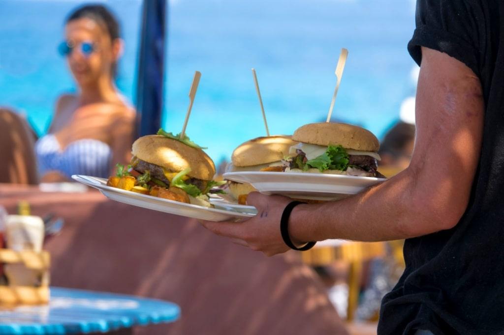 Kellner serviert Cheeseburger auf Terrasse eines Restaurants