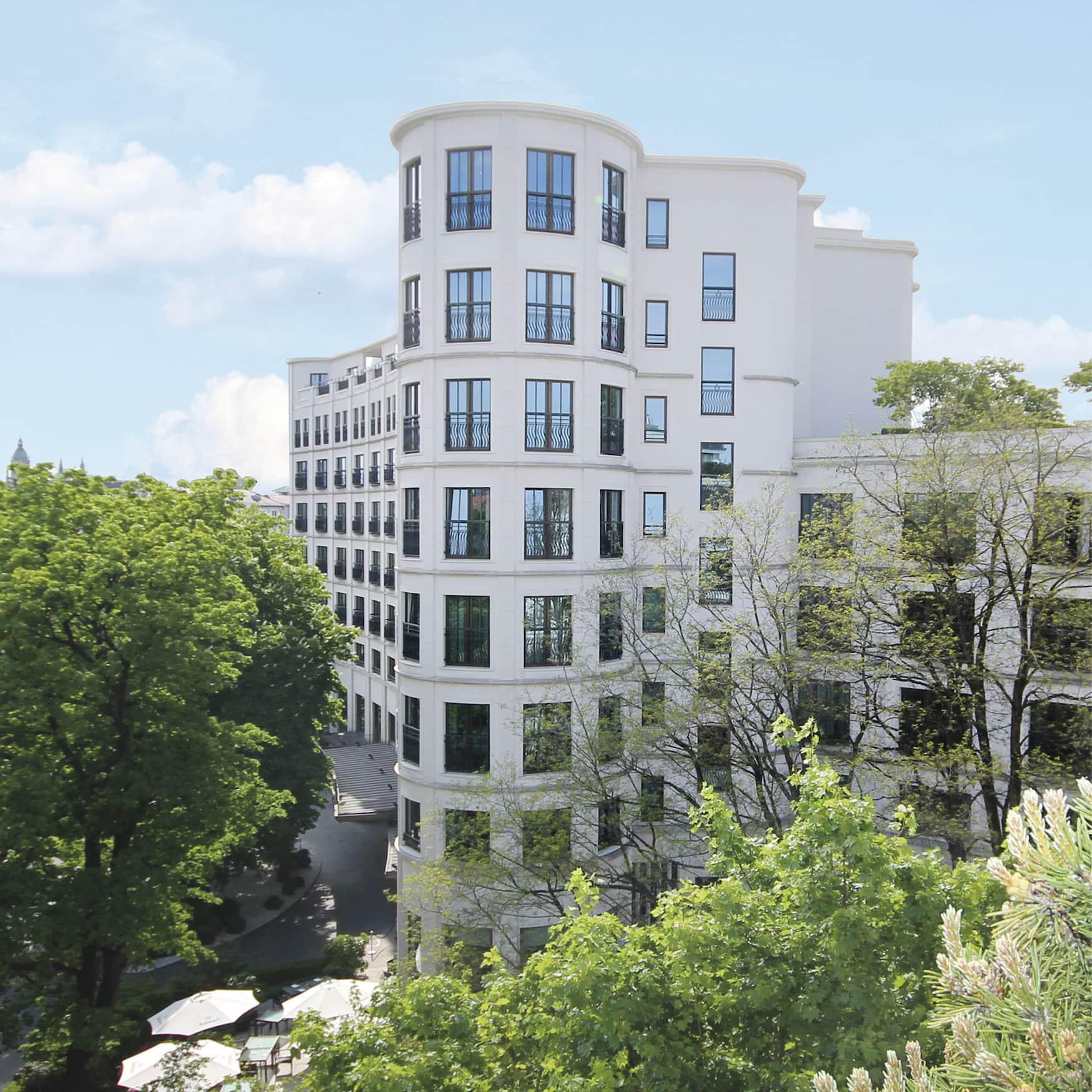 Außenfassade eines Grandhotels in München umgeben von grünen Bäumen