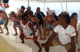 Einheimische und Touristen tanzen gemeinsam Merengue auf einem Boot an der Punta Cana