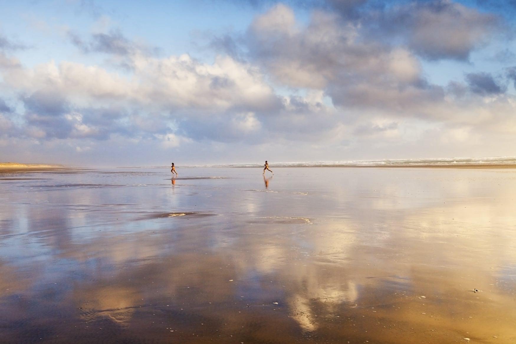 Zwei Frauen springen am Wasser entlang am Ninety Mile Beach in Neuseeland