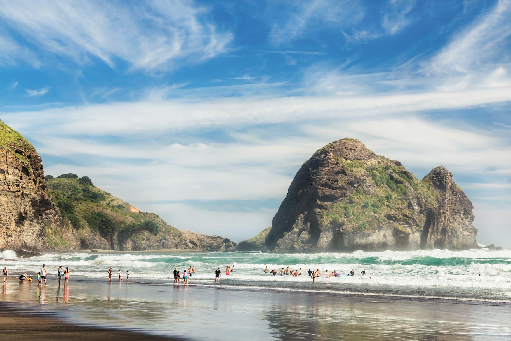 Surfer am Piha Beach, einem der schönsten Strände in Neuseeland