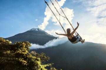 Frau auf einer Schaukel über den Bergen iN Ecuador
