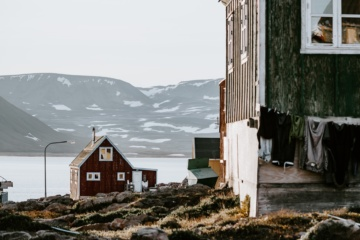 Zwei Holzhütten stehen vor verschneiter Landschaft auf Grönland