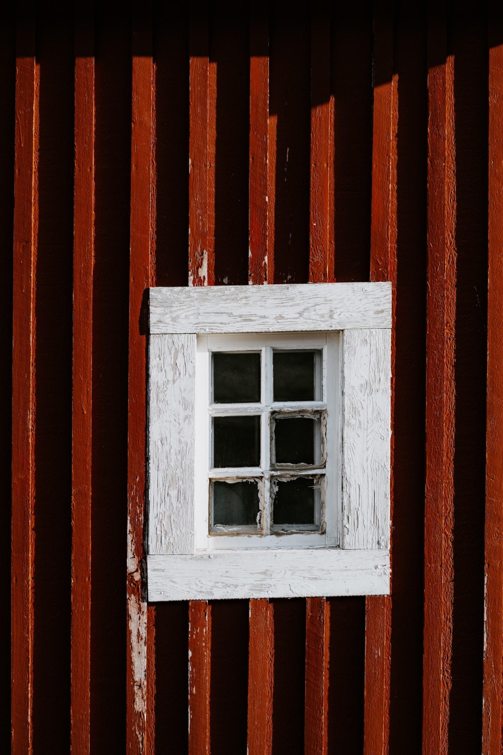Weißes Fenster auf rotem Holzhaus