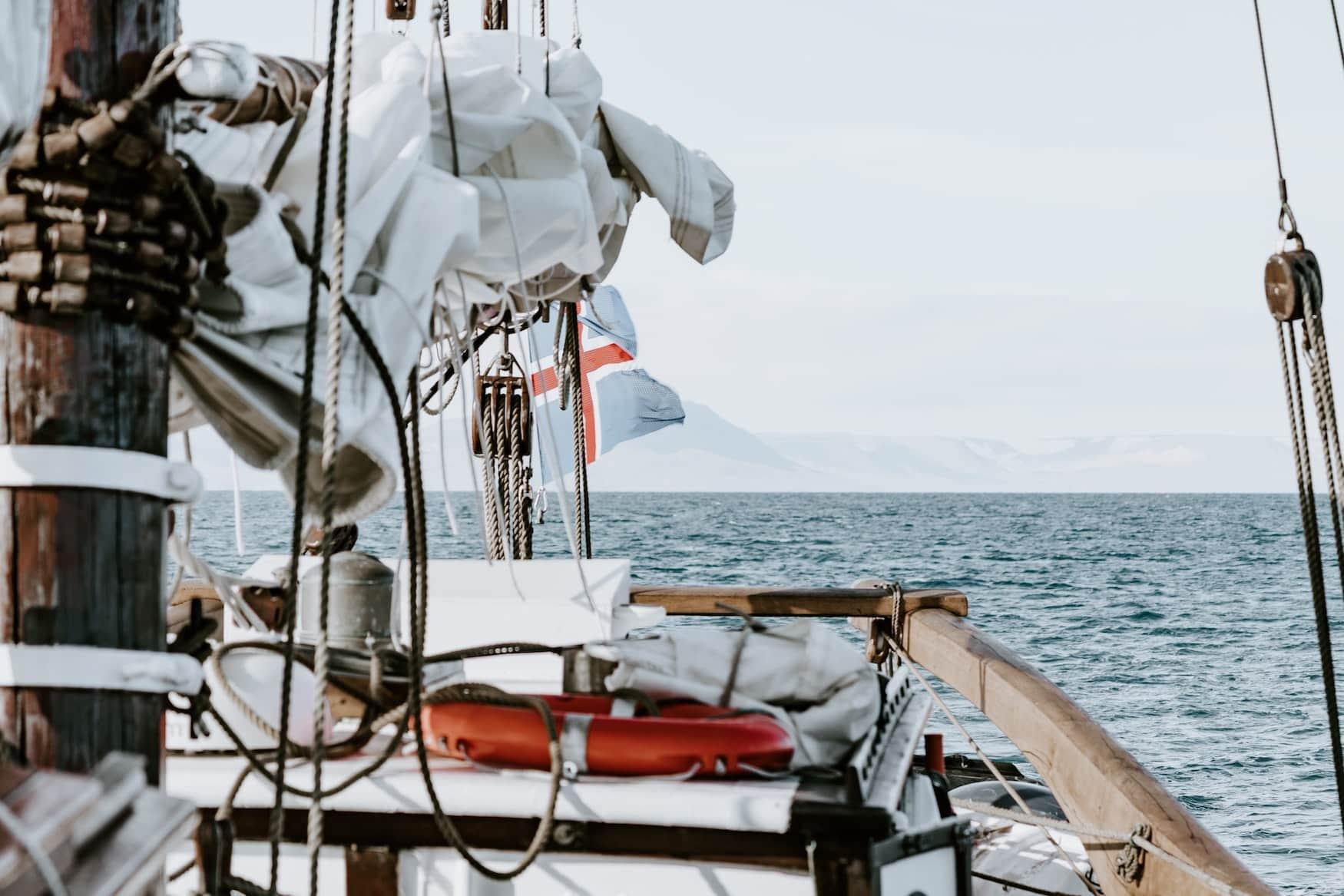 Segelschiff fährt auf offenem Gewässer. Grönland Flagge weht im Wind