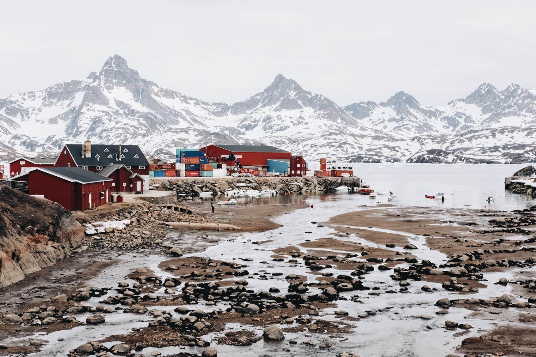 Rote Holzhütten stehen in verschneiter Landschaft in Grönland