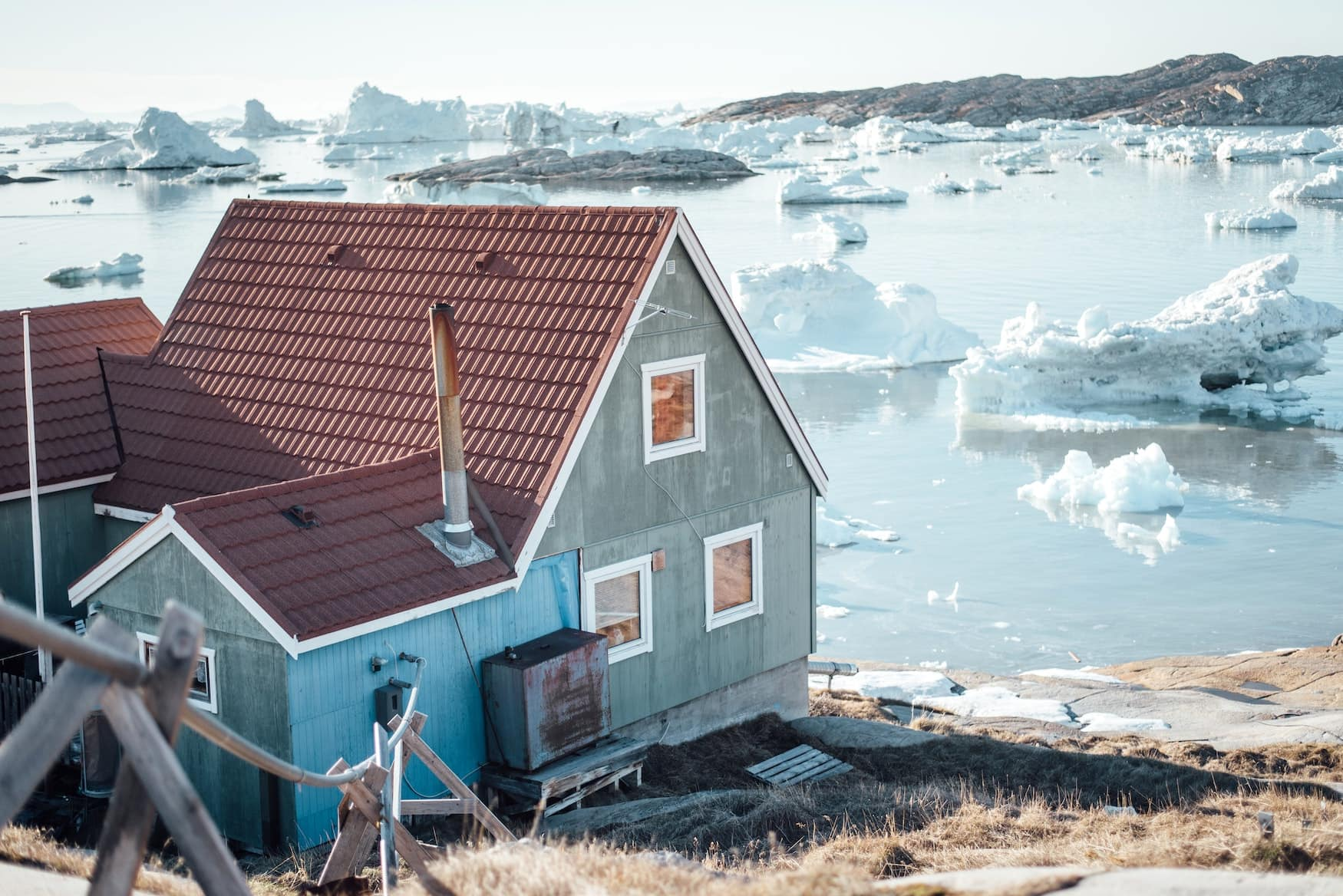 Bunte Holzhütte steht vor Gewässer mit Gletschern