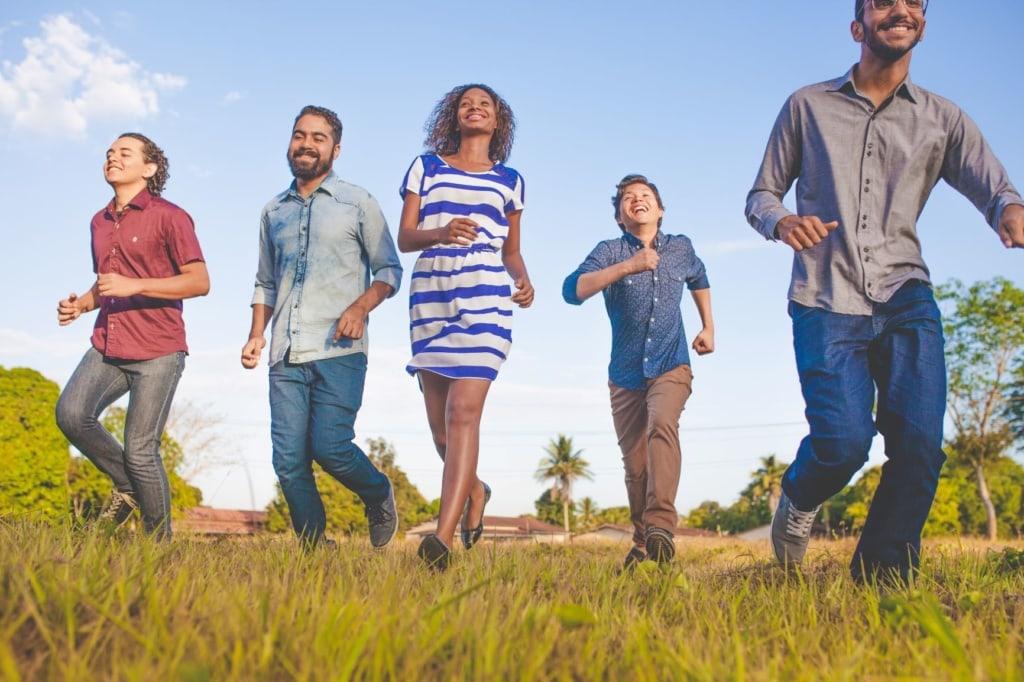 Gruppe junger Menschen läuft über Wiese