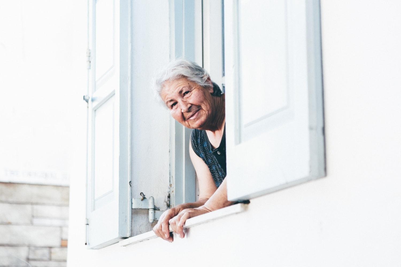 Griechische ältere Dame guckt aus dem Fenster