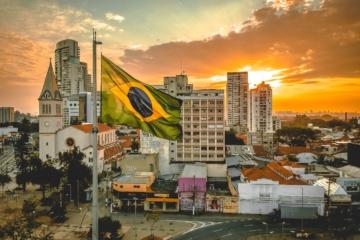 Brasilianische Flagge im Wind vor Skyline