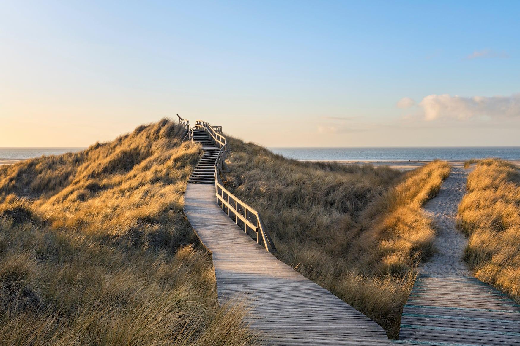 hölzerner Steg durch die Dünen zum Strand Norddorf auf der deutschen Nordseeinsel Amrum