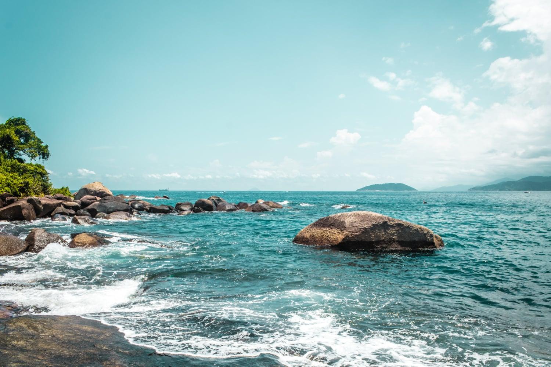 Türkisfarbenes Meer prallt gegen Steine vor der Küste der Ilhabela in Brasilien