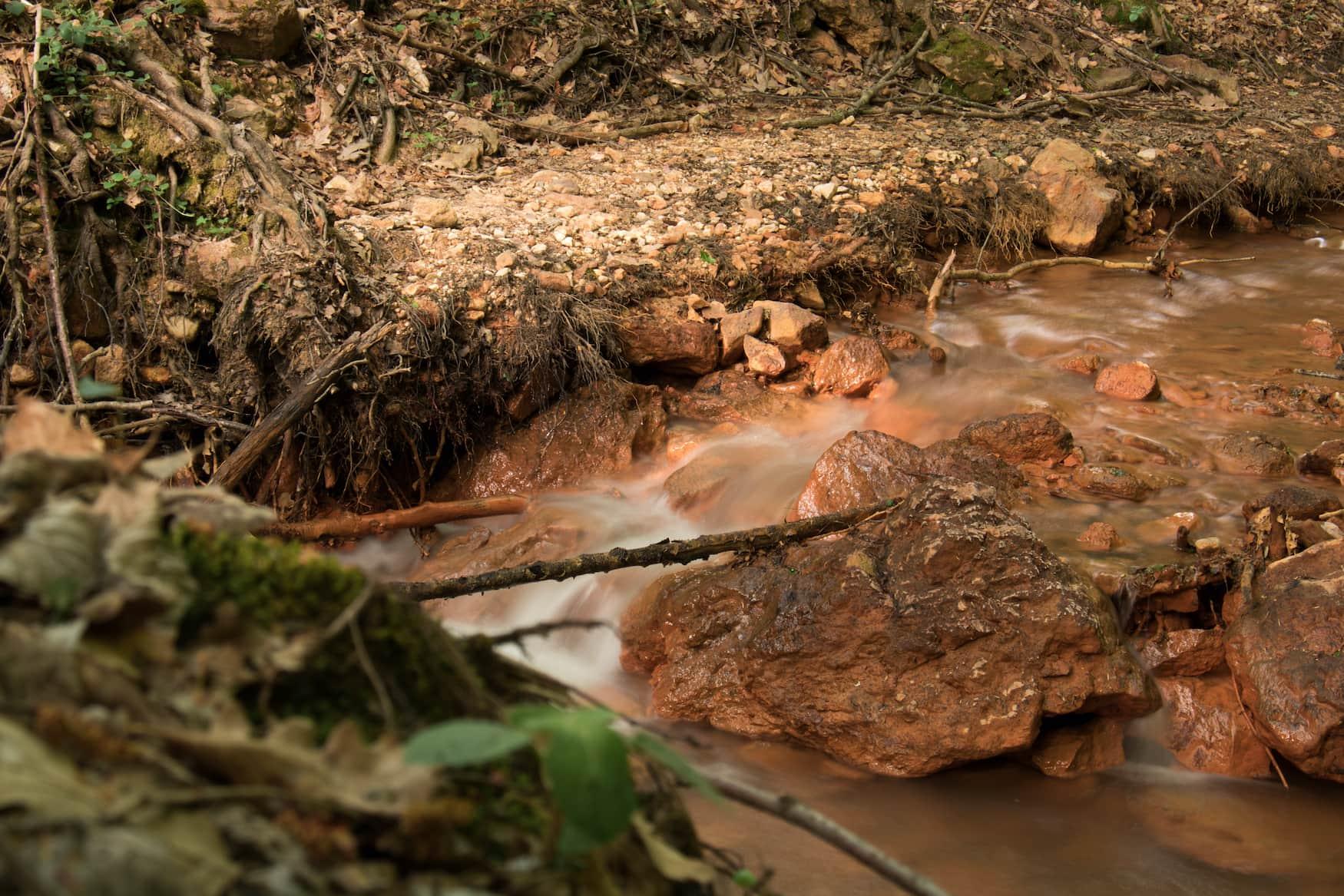Rötliches Wasser fließt durch einen Fluss  in Serbien