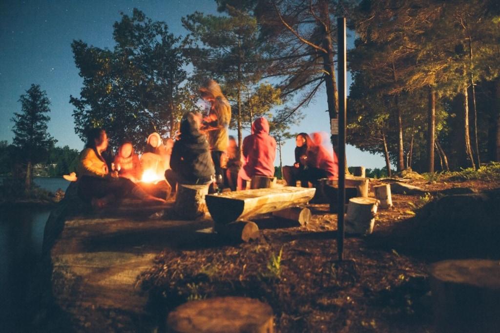 Besucher eines Campingplatzes sitzen abends im Kreis am Feuer