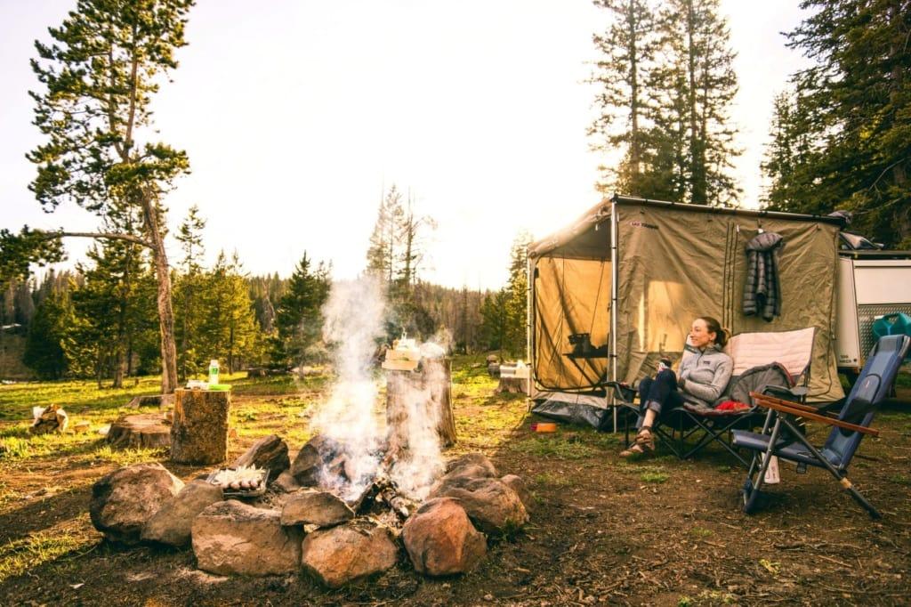 Frau sitzt auf Stuhl neben ihrem Campingzelt
