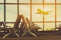 Sitzreihe im Flughafen-Terminal mit Blick auf abhebendes Flugzeug