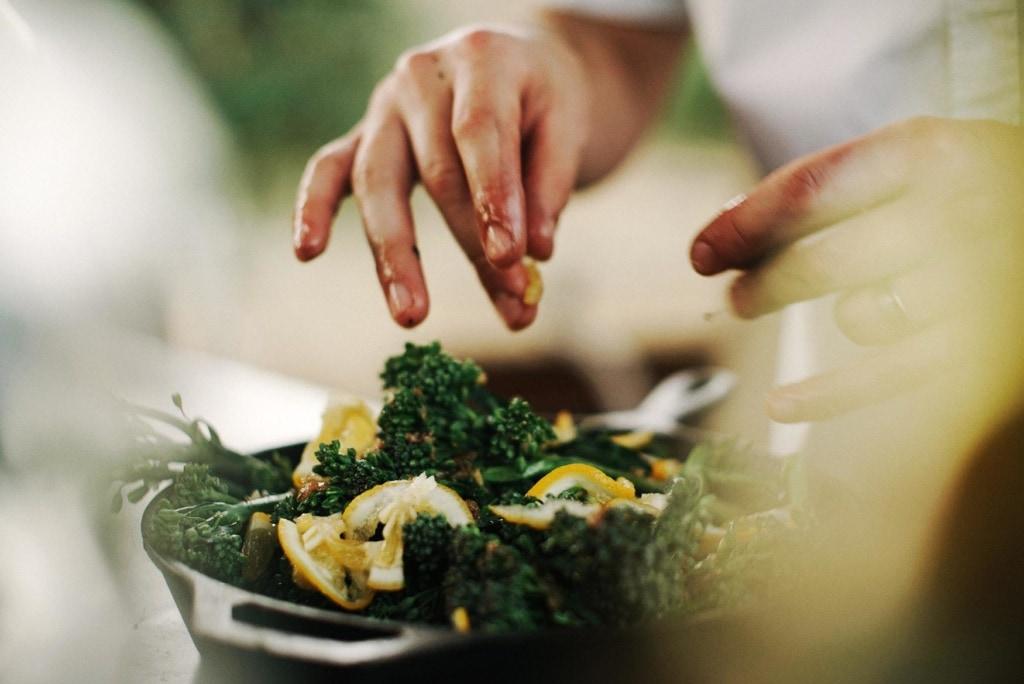 Frau arrangiert mit den Händen die Deko eines Meeresfrüchtesalats