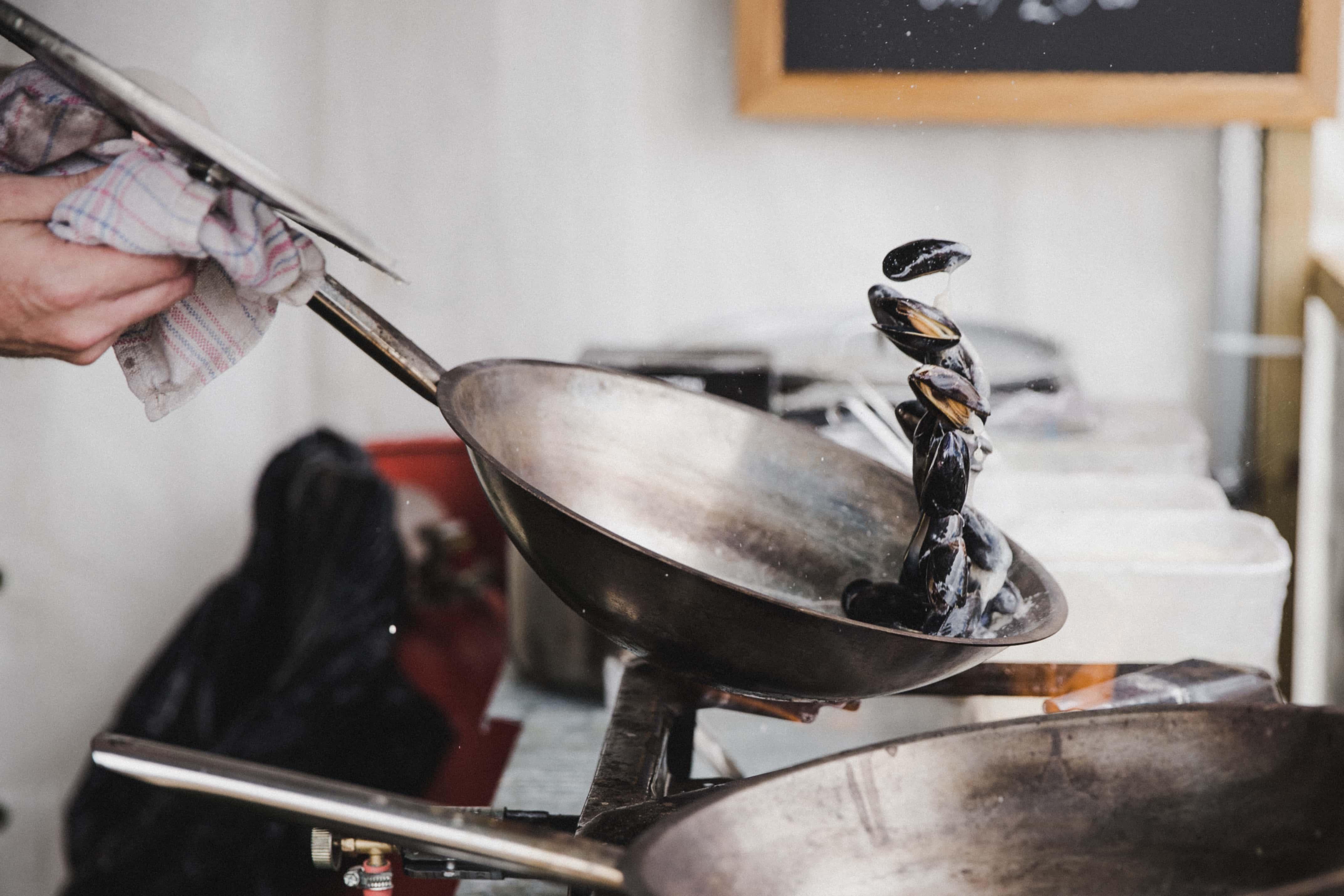 Koch schwenkt Muscheln in Pfanne beim Food & Fun Festival in Island