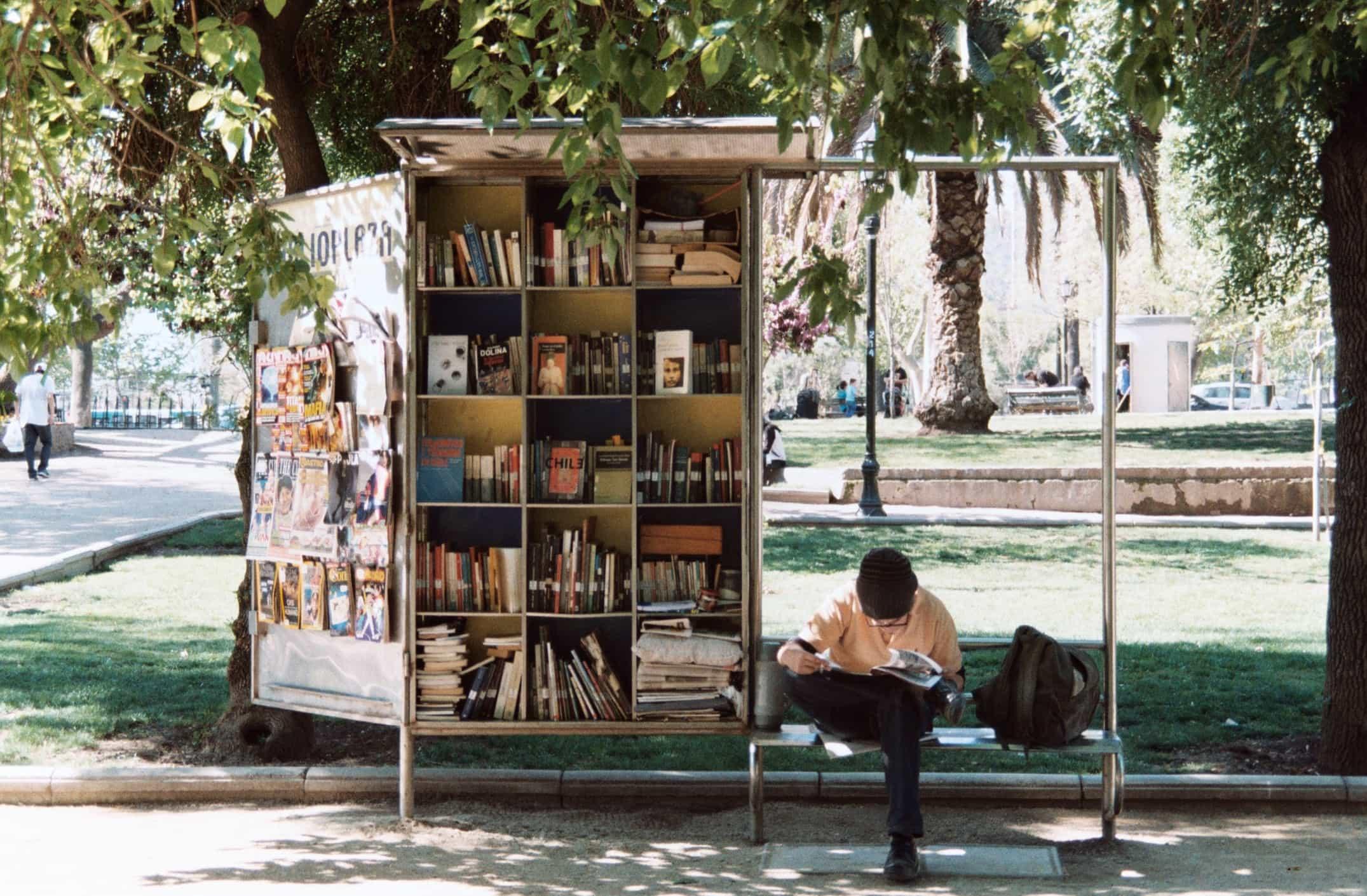 Junger Mann sitzt auf einer Bank in Santiago de Chile und liest ein Buch