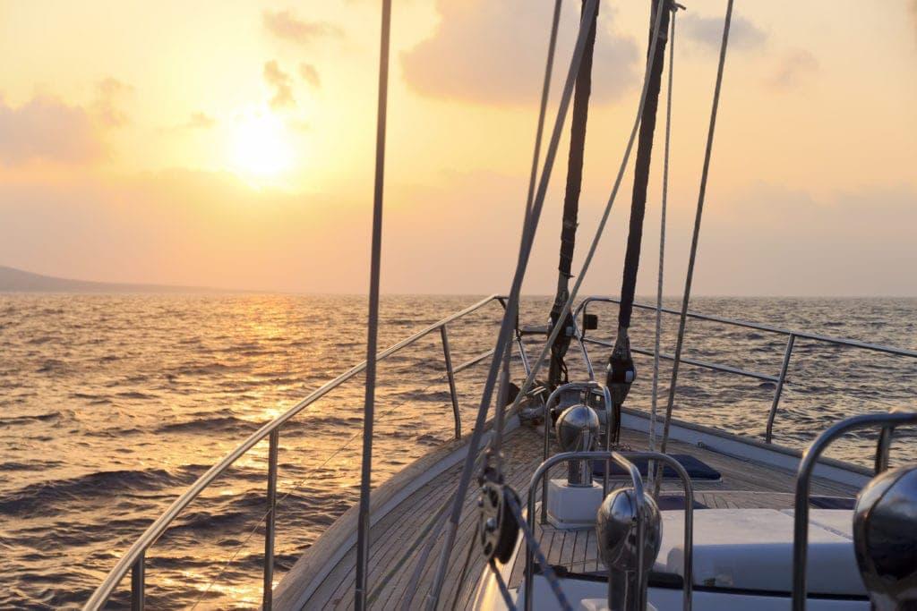 Sport im Urlaub: Segelboot bei Sonnenuntergang
