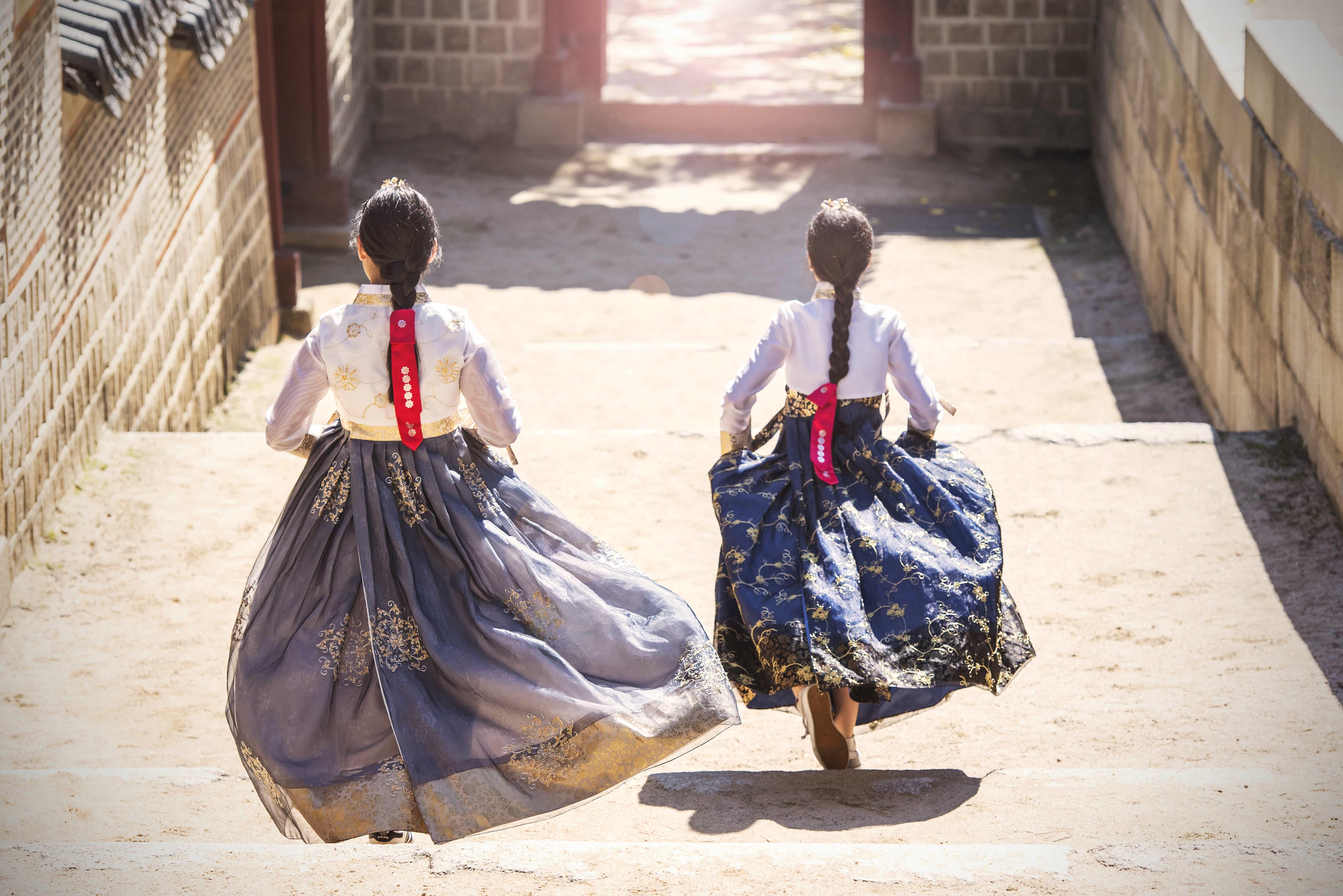 Mädchen in traditioneller südkoreanischer Kleidung laufen Treppen hinab