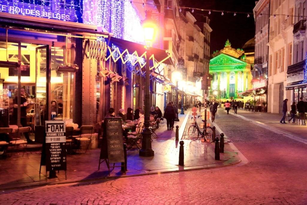 Abendliche Straßenszene in Brüssel, mit Restaurant links