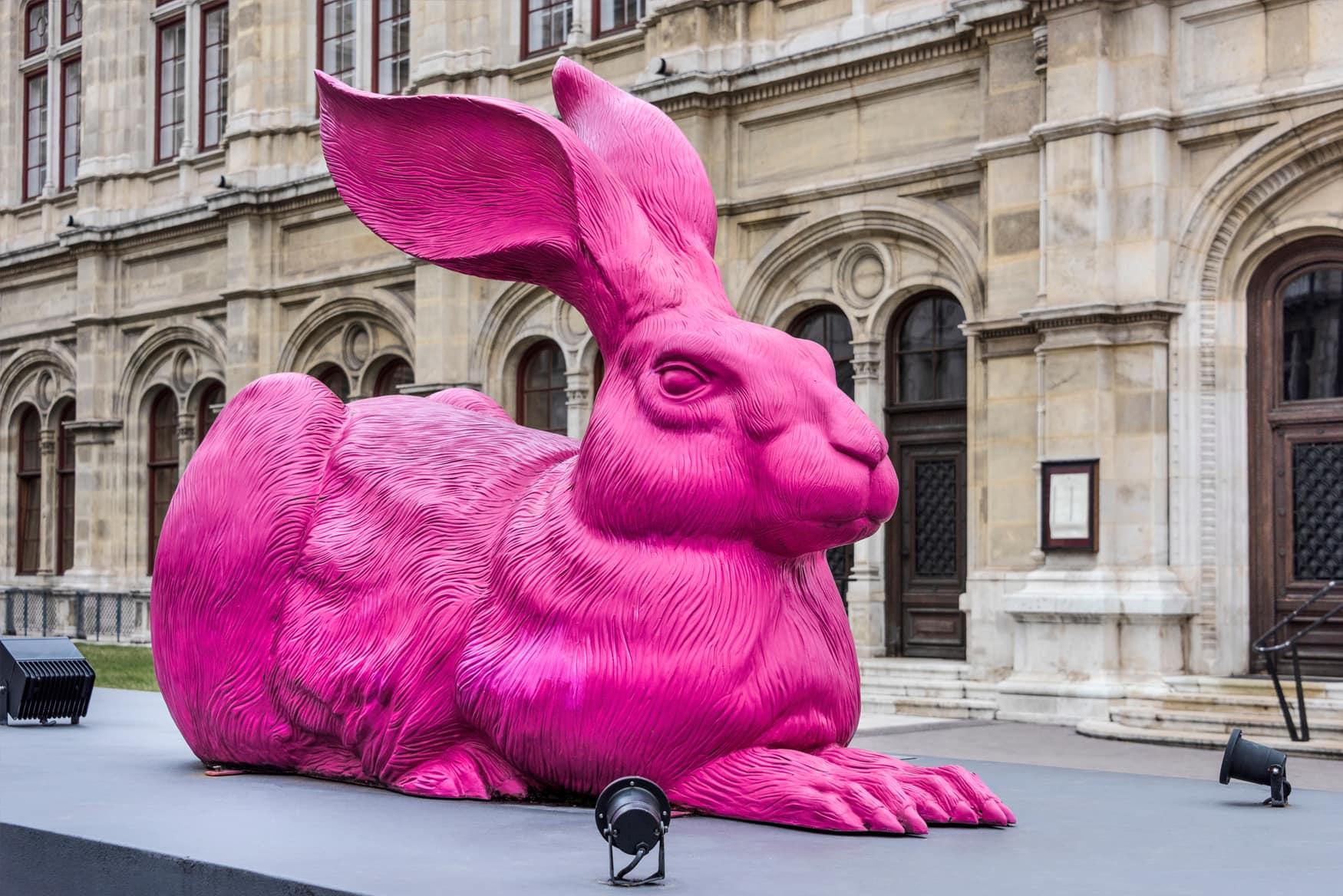Kunstwerk »Der Feldhase« als pinke Hasen Skulptur neben Wiener Staatsoper