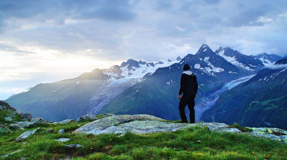 Alpenpanorama und junger Mann bei Dämmerung