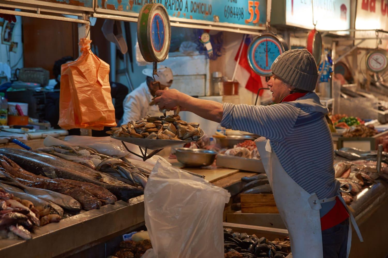 Chilenischer Mann wiegt Fisch in Markthalle