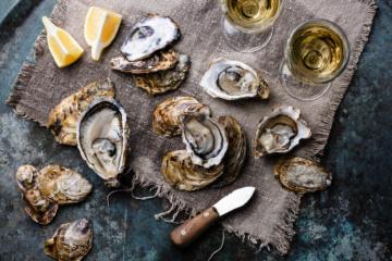 Austern serviert mit Weißwein und Zitrone
