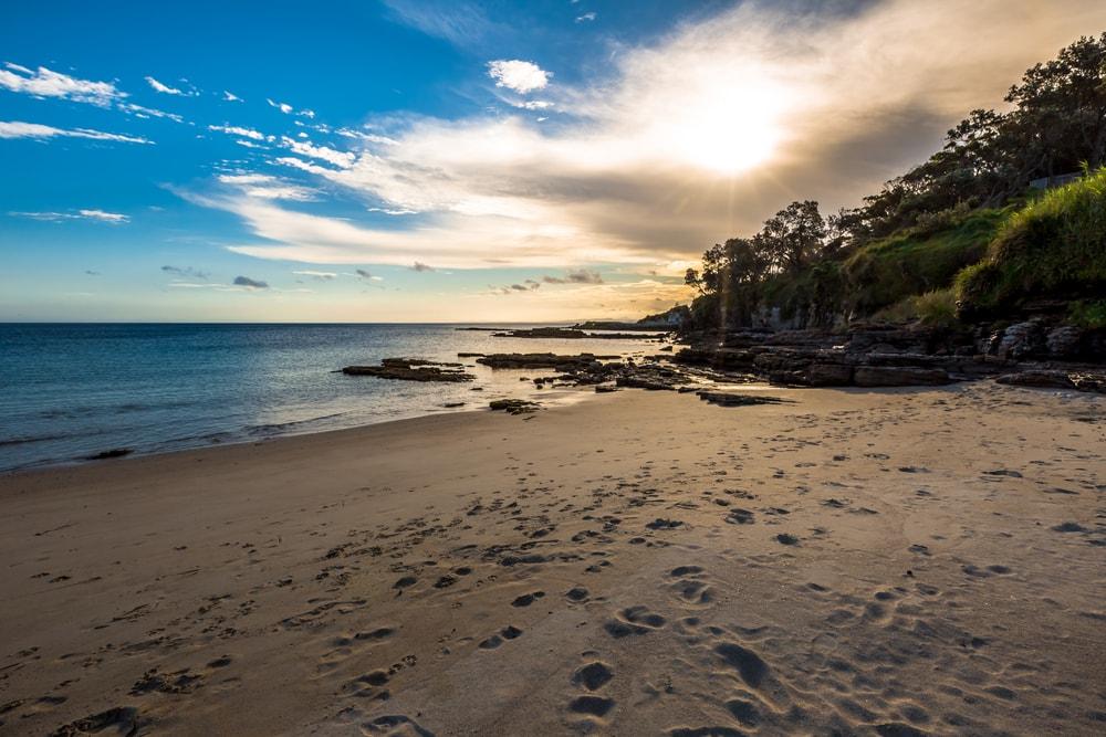 Tropischer, wilder Strand mit Bäumen und Felsen