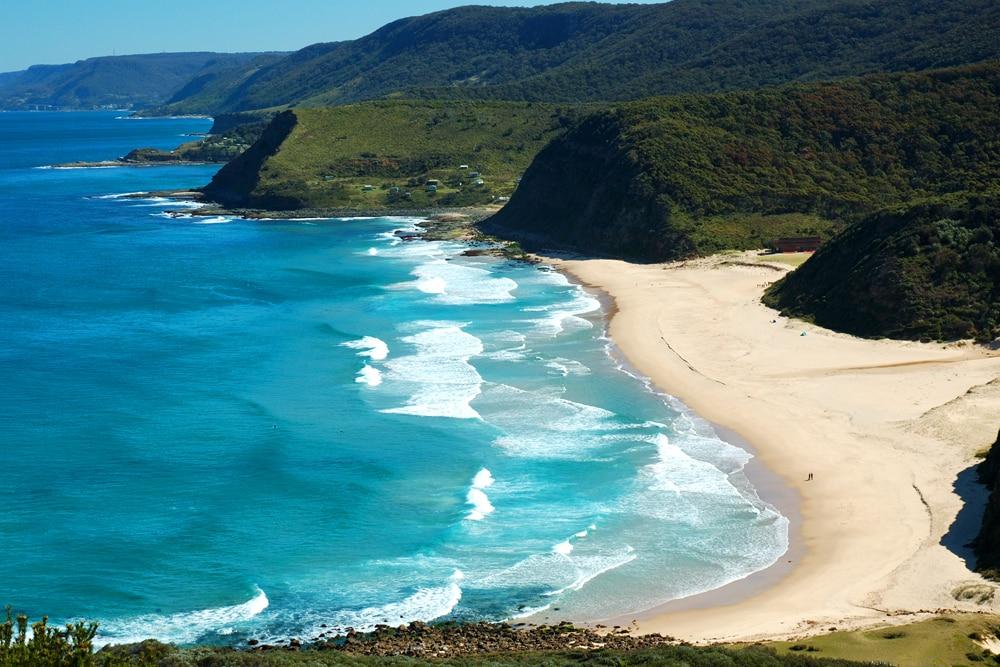 Weißer Strand an Ozean und bewachsenen Hügeln