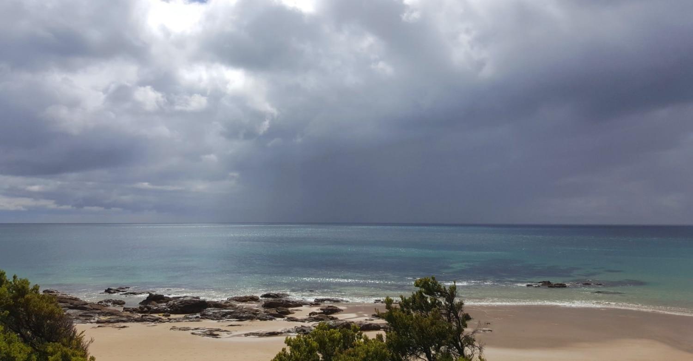 Wilder, tropischer Strand mit feinem Sand und Felsen