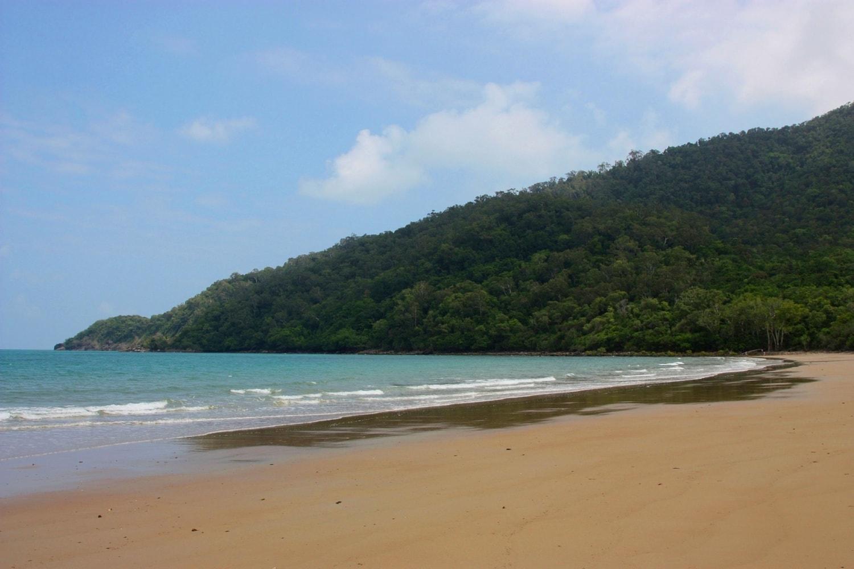 Einsamer Strand mit feinem Sand und Bäumen