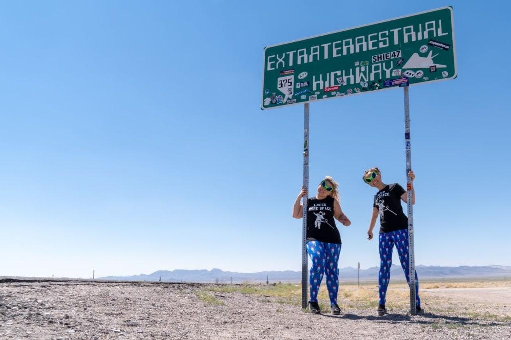 Zwei Frauen posieren vor einem Schild auf der Route 375 in Nevada
