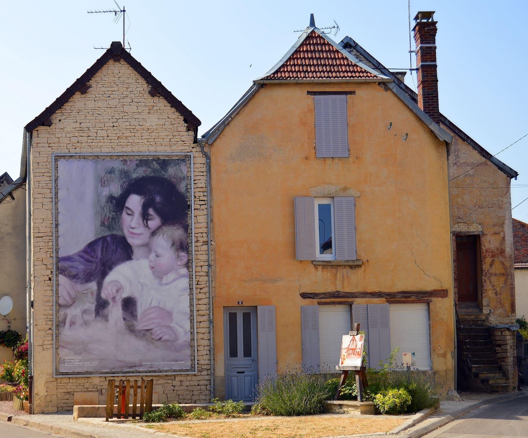 Bild von einer Straße in Essoyes in Frankreich, wo große Reproduktionen des berühmten Malers Renoir das Straßenbild schmücken.