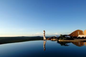 Frau spaziert über Infinity Pool vor Landschaftskulisse Kenias