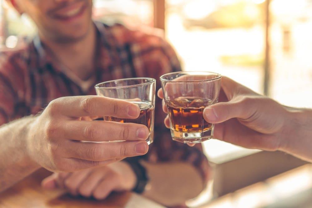 Mann stößt mit Whiskey-Glas an