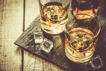 Whiskey-Gläser auf schwarzem Tablett, Foto im Retro-Style