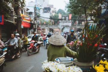 Frau mit Reishut schiebt ihr Fahrrad durch Straßen von Hanoi