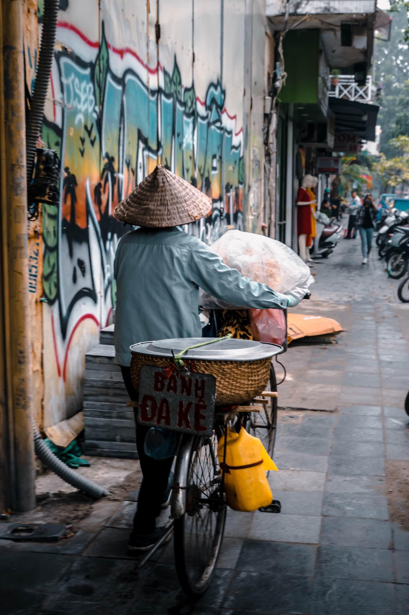 Einheimischer in Hanoi, Vietnam, fährt mit Fahrrad und trägt einen typischen Reishut